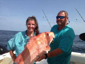 Man and woman holding red snapper | Frazier's Guide Service